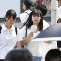 People walk amid the scorching summer heat in Nagoya on Aug. 2. | KYODO