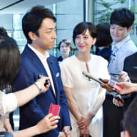 Liberal Democratic Party lawmaker Shinjiro Koizumi and TV personality Christel Takigawa speak to reporters outside the Prime Minister's Office on Aug. 7. | KYODO