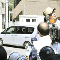 A car carrying a man suspected of instigating a road rage incident leaves a police station in Osaka. | KYODO