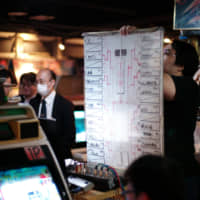 An emcee holds up a bracket for a tournament at the Mikado amusement arcade in Tokyo's Takadanobaba district earlier this year. | RYUSEI TAKAHASHI