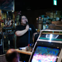 An emcee commentates on proceedings during a tournament at the Mikado amusement arcade in Tokyo's Takadanobaba district earlier this year. | RYUSEI TAKAHASHI