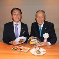 Tottori Gov. Shinji Hirai (left) and Fujiya Co. Chairman Kensuke Yamada introduce some samples of the delectable dishes at Tottori Wagyu Daisen Fujiya Shinsaibashi Honten in Osaka on July 6. | MASAAKI KAMEDA