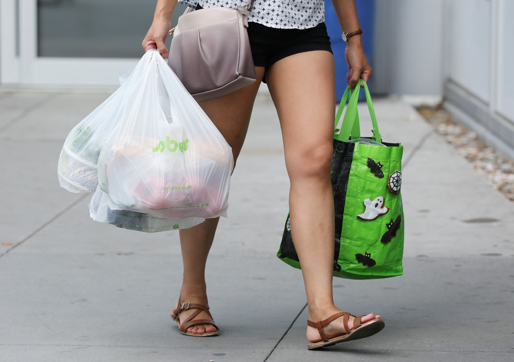 A woman leaves a supermarket with both plastic bags and a reusable bag. Since California banned 'single-use' plastic bags, sales of small plastic trash bags have risen 120 percent . | REUTERS