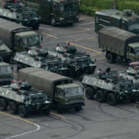 Trucks and armored personnel carriers are seen parked in Shenzhen, bordering Hong Kong, on Aug. 16. | AFP-JIJI