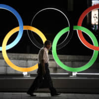 A man walks by a display of the Olympic rings in Tokyo on July 23. | AP