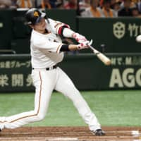 Giants captain Hayato Sakamoto slugs a solo home run in the first inning against the Tigers on Saturday afternoon at Tokyo Dome. Yomiuri topped Hanshin 4-2. | KYODO