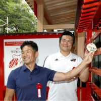 Former Brave Blossoms captain Toshiaki Hirose (left) visits a rugby shrine in Tokyo's Marunochi business district on Tuesday, a month before the Rugby World Cup starts in Japan. The shrine will be open to the public until the end of the tournament. | KYODO