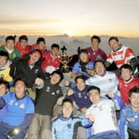 Yamanashi Gakuin University rugby players pose for a photo with the Webb Ellis Cup at the summit of Mt. Fuji on Tuesday as part of the trophy's tour around the country ahead of the Rugby World Cup, which begins on Sept. 20. | KYODO