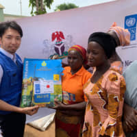 A UNDP staffer provides agricultural tools, fertilizer and seeds to community members in Michika, Yobe state, Nigeria. | UNITED NATIONS DEVELOPMENT PROGRAMME