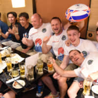 Supporters of Russia's men's rugby team, including members of the Moscow State University Rugby Club, drink at a pub in Tokyo's Shinjuku on Thursday night. | DAN ORLOWITZ