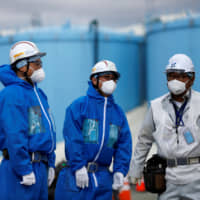 Workers stand in front of storage tanks for radioactive water at the tsunami-crippled Fukushima No. 1 nuclear power plant in Okuma, Fukushima Prefecture, in February. | REUTERS