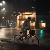 A man rides his bicycle in heavy rain as a typhoon hits Tokyo. | AFP-JIJI