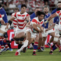 Japan's Shota Horie is tackled by a Russian player during the Rugby World Cup Pool A game at Tokyo Stadium between Russia and Japan on Sept. 20. | AP