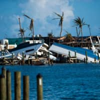 Destroyed boats are pushed up against the pier in the aftermath of Hurricane Dorian in Treasure Cay on Abaco island, Bahamas, Wednesday. | AFP-JIJI