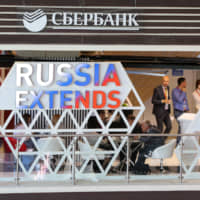 A Sberbank of Russia PJSC logo sits displayed above a corporate stand during the opening day of the Eastern Economic Forum in Vladivostok, Russia, on Wednesday. | BLOOMBERG