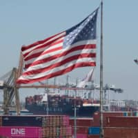 The U.S. flag flies over a container ship unloading cargo from Asia at the Port of Long Beach, California, on Aug. 1. China on Wednesday said it would spare a number of U.S. products from punitive tariffs in what is seen as an olive branch by Beijing in the protracted trade war ahead of high-level talks next month. | AFP-JIJI