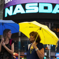 Women walk past the Nasdaq MarketSite in New York's Times Square in 2013. | REUTERS