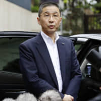 Nissan Motor Co. CEO Hiroto Saikawa speaks to reporters outside his home in Tokyo on Monday. | KYODO
