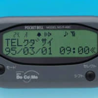 A pager from NTT Docomo Inc. displays a text message saying 'please call.' | NTT DOCOMO INC. / VIA KYODO