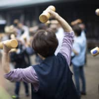 People holding wooden dumbbells exercise during an event at a temple in the Sugamo district of Tokyo. | BLOOMBERG
