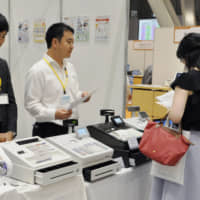 Cash registers that can compute prices for items subject to differing tax rates are displayed in Tokyo in June. | KYODO