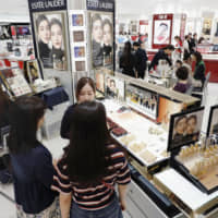 People shop for cosmetics at the Matsuya department store in Tokyo's Ginza district on Sunday ahead of Tuesday's consumption tax hike. | KYODO