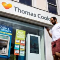 Pedestrians walk past a Thomas Cook travel agent's shop in London in mid-July. The tour operator has confirmed it is seeking £200 million in extra funding as it attempts to prevent its collapse. | AFP-JIJI