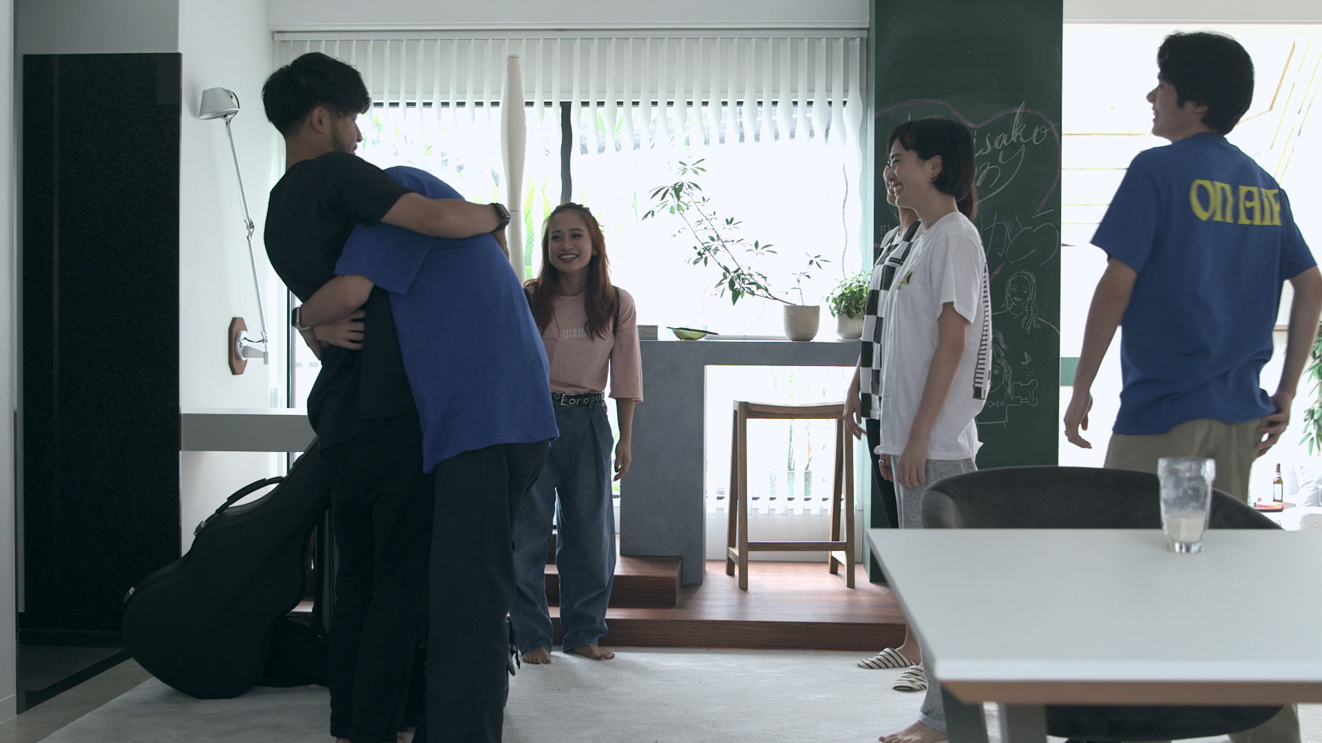 Sweet sorrow: Kenny (left) receives a tight hug from roommate Ruka before his departure from 'Terrace House Tokyo 2019-2020.' | © FUJI TELEVISION / EAST ENTERTAINMENT