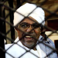 Former President Omar Hassan al-Bashir smiles inside a courthouse cage in Khartoum on Saturday. | REUTERS