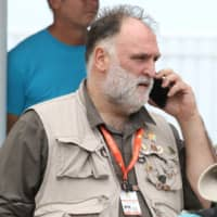 Jose Enrique, founder of World Kitchen Central, speaks on a cellphone at Odyssey Aviation in Nassau Tuesday. | JOHN MARC NUTT / VIA REUTERS