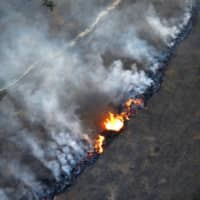 A fire burns in an area of the Amazon rainforest near Porto Velho, in the Brazilian state of Rondonia, on Sept. 10. | REUTERS