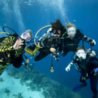 Diana Ademic (left), Berenice Felipa, Steve Salika and Tia Salika (right) enjoy a dive during their November 2018 Thanksgiving trip at a Kids Sea Camp week at Buddy Dive Resort off Bonaire, a Netherlands-administered island in the Leeward Antilles off the coast of Venezuela. All four were aboard the dive boat Conception and all died in the fire that swept the vessel on Sept. 2 off Southern California. The photo was provided by Margo Peyton. | AP