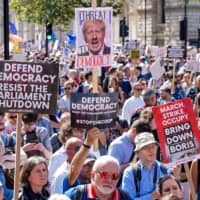 Demonstrators hold up placards during a protest outside Downing Street in London on Saturday against Prime Minister Boris Johnson's move to suspend Parliament in the final weeks before Brexit. | AFP-JIJI