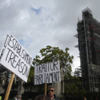 Brexit supporters hold placards outside the scaffolded tower known as Big Ben at the Houses of Parliament in London Thursday. British Prime Minister Boris Johnson faced a backlash from furious lawmakers Thursday over his use of charged and confrontational language in Parliament about opponents of his Brexit plan. | AP