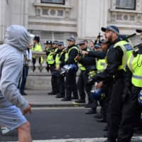 Demonstrators clash with police at Whitehall Saturday during an anti-government protest calling for the prime minister's resignation, near Downing Street in central London. Britain's upper house on Friday gave final approval to a law that would force Boris Johnson to delay Brexit, in a fresh setback for Johnson, who is struggling in his bid to call an early election. | AFP-JIJI