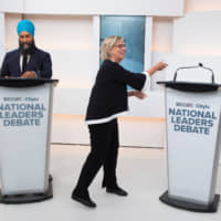 Green Party leader Elizabeth May mimes shaking hands with an absent Prime Minister Justin Trudeau, who chose not to attend the Maclean's/Citytv National Leaders Debate last Thursday in Toronto. | REUTERS