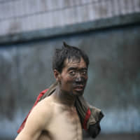 A Chinese coal miner emerges from a mine at the end of a shift in Liulin, Shanxi province, in this file photo. | BLOOMBERG NEWS