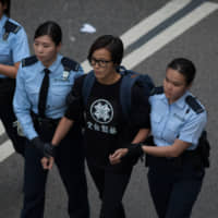Denise Ho, singer and activist, is arrested by police in Hong Kong in December 2014. Ho said Beijing is using its power and influence to quash dissent around the world, and urged businesses who invest in China and Hong Kong to support human rights and democracy. | BLOOMBERG