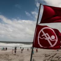 Red flags to indicate the ocean has a high tide and locals should not be swimming due to danger are seen at Jacksonville Beach before Hurricane Dorian, in Jacksonville, Florida, Tuesday. | REUTERS