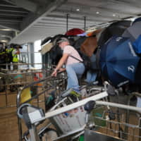 A passenger climbs over barriers as pro-democracy protesters block entrances outside the airport in Hong Kong on Sunday. | AP