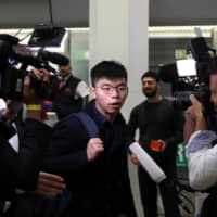 Hong Kong's pro-democracy activist Joshua Wong is surrounded by journalists after arriving at Tegel Airport in Berlin, Germany, on Monday. | REUTERS
