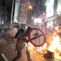 A protester uses a shield to cover himself as he faces policemen in Hong Kong on Saturday on a street that runs through the bustling Causeway Bay shopping district. | AP