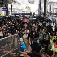 Pro-democracy protesters gather outside the gate of the Hong Kong Airport on Sunday. | REUTERS