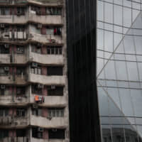 A dilapidated apartment building stands alongside a gleaming modern tower in Hong Kong.   AP
