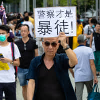 A demonstrator holds a placard reading 'police are actual rioters' during a rally in Hong Kong on Tuesday. | BLOOMBERG