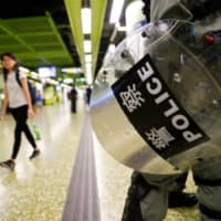 A riot policeman holds his shield for protection at a Mass Transit Railway station in Hong Kong on Monday. | REUTERS