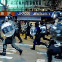 Police chase protesters during a demonstration on Nathan Road in Hong Kong on Friday. | AP