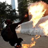 An anti-government protester throws a petrol bomb during a demonstration near the Central Government Complex in Hong Kong on Sunday. | REUTERS