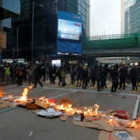 Protestors leave after lighting a fire on a road during a rally in Hong Kong on Sunday. | REUTERS