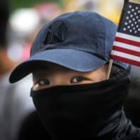A protester takes part in a march from Chater Garden to the U.S. Consulate in Hong Kong on Sunday. | AFP-JIJI